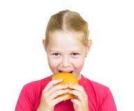 Niña que come la hamburguesa. Fotografía de archivo