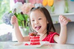 Niña que come la torta de la fresa Imagen de archivo