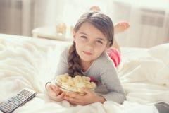 Niña que come las palomitas en cama Fotos de archivo