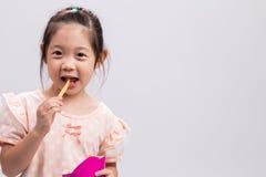 Niña que come las patatas fritas/niña que come el fondo de las patatas fritas imágenes de archivo libres de regalías