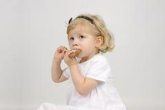 Niña que come un lollypop del chocolate Imagenes de archivo