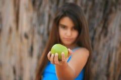 Niña que come una manzana verde Fotos de archivo