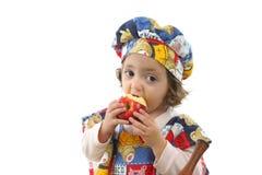 Niña que come una manzana vestida como cocinero Imagenes de archivo