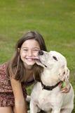 Niña que consigue beso de perro Imagen de archivo