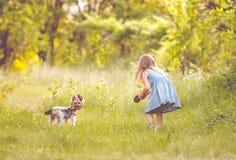 Niña que corre con el perro en el campo Fotografía de archivo libre de regalías