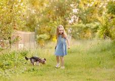 Niña que corre con el perro en el campo Fotografía de archivo
