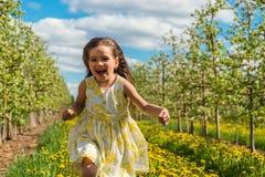 Niña que corre en el medio de una manzana orchar Fotografía de archivo libre de regalías