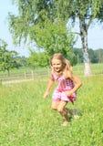 Niña que corre en prado Imagen de archivo libre de regalías