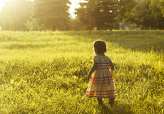 Niña que corre en prado con puesta del sol Foto de archivo