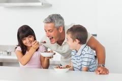 Niña que da el cereal a su padre con la sonrisa del hermano Imágenes de archivo libres de regalías