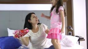 Niña que da un regalo a su madre en el dormitorio Ella la cierra los ojos almacen de video