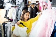 Niña que decide sobre el vestido bonito Fotografía de archivo libre de regalías
