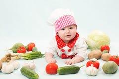 Niña que desgasta un sombrero del cocinero con las verduras Imagenes de archivo