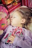 Niña que duerme con el bastón de caramelo de la Navidad Fotografía de archivo
