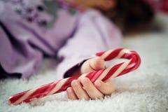 Niña que duerme con el bastón de caramelo en su mano Fotos de archivo libres de regalías