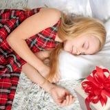 Niña que duerme con el regalo ¡Los sueños vienen verdad! Imagen de archivo libre de regalías