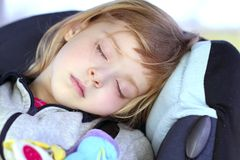 Niña que duerme en asiento de la seguridad del coche de los niños