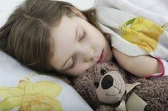 Niña que duerme en cama con el oso de peluche Imagenes de archivo