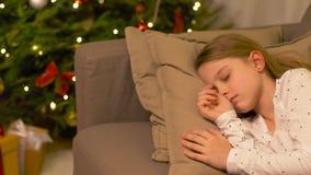 Niña que duerme en el sofá cerca del árbol de navidad metrajes