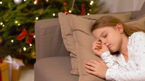 Niña que duerme en el sofá cerca del árbol de navidad almacen de metraje de vídeo