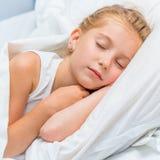 Niña que duerme en la cama blanca Imagen de archivo libre de regalías
