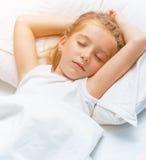 Niña que duerme en la cama blanca Imágenes de archivo libres de regalías