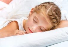 Niña que duerme en la cama blanca Foto de archivo