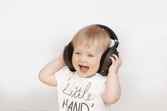 Niña que escucha la música en los auriculares Fotografía de archivo