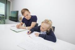 Niña que estudia mientras que se sienta por el padre en la tabla Fotografía de archivo libre de regalías