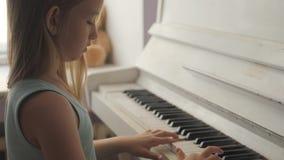 Niña que estudia para jugar el piano en casa Ni?o preescolar que se divierte con el aprendizaje tocar el instrumento de m?sica almacen de video