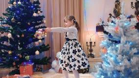 Niña que gira con las decoraciones de la Navidad almacen de metraje de vídeo