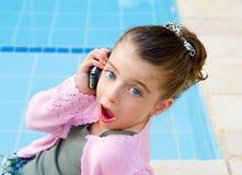 Niña que habla el teléfono móvil con sorpresa fotos de archivo