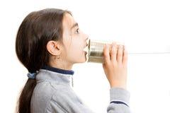 Niña que habla en el teléfono construido con el tarro fotos de archivo