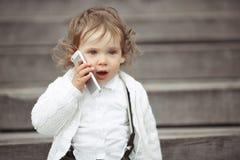 Niña que habla en el teléfono móvil Fotos de archivo