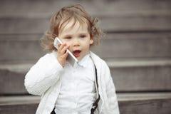 Niña que habla en el teléfono móvil Fotografía de archivo