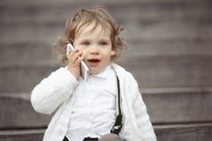 Niña que habla en el teléfono móvil Imagenes de archivo