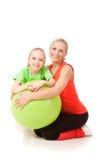 Niña que hace ejercicio con un instructor Foto de archivo libre de regalías