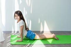Niña que hace la gimnasia en un bozal verde del perro de la actitud de la yoga de la estera para arriba imagen de archivo libre de regalías