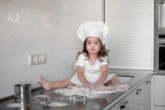 Niña que hace la pasta y las galletas en cocina imagen de archivo libre de regalías