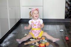 Niña que hace la pasta y las galletas en cocina foto de archivo