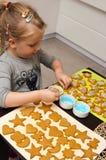 Niña que hace las galletas de la Navidad Imagenes de archivo