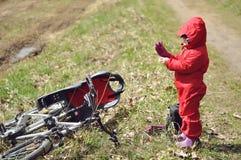 Niña que hace una pausa la bicicleta con un asiento del niño foto de archivo