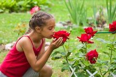 Niña que huele rosas rojas hermosas en un jardín Imágenes de archivo libres de regalías