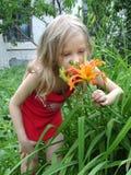 Niña que huele una flor Fotos de archivo