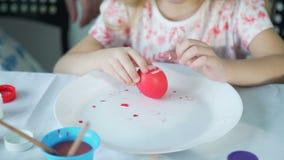 Niña que intenta a pelar el huevo de Pascua colorido almacen de video