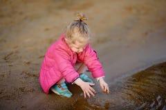 Niña que juega con agua y el palillo durante paseo por el lago Imagen de archivo