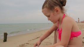 Niña que juega con arena de mar almacen de video