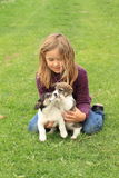 Niña que juega con dos perritos Fotografía de archivo