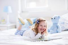 Niña que juega con el juguete y que lee un libro en cama Imagen de archivo libre de regalías