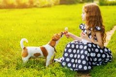 Niña que juega con el perrito en parque imagenes de archivo
